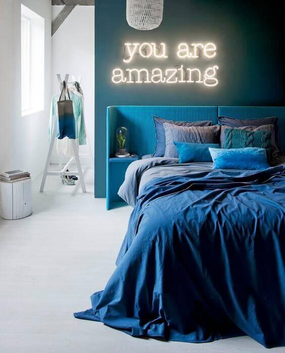 Mavi tonlarında yatak odası ve neon yazı