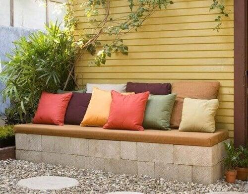 beton bir bankın üstüne konmuş rengarenk yastıklar