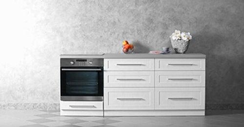 gri duvar önünde bayz çekmeceli dolaplar ve beyaz çekmeceli siyah fırın