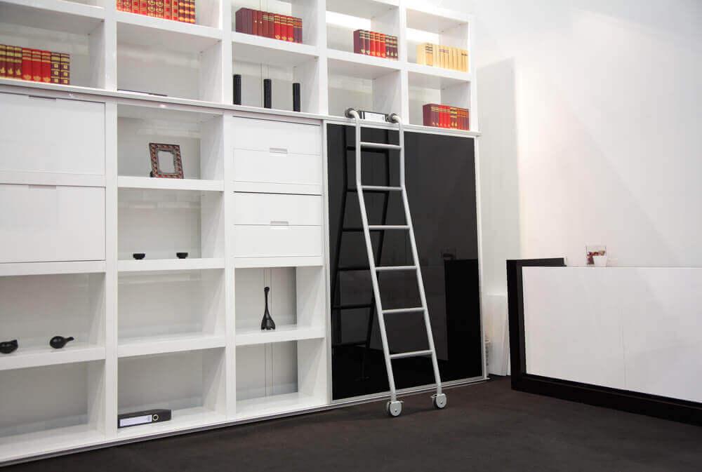Bir duvarı kaplayan beyaz renkli evde kütüphane