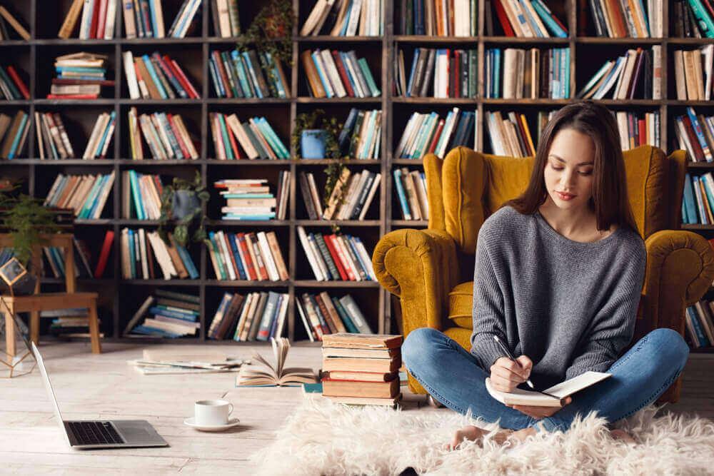 Kütüphanenin bulunduğu odada sarı koltuk önünde yere oturan kadın
