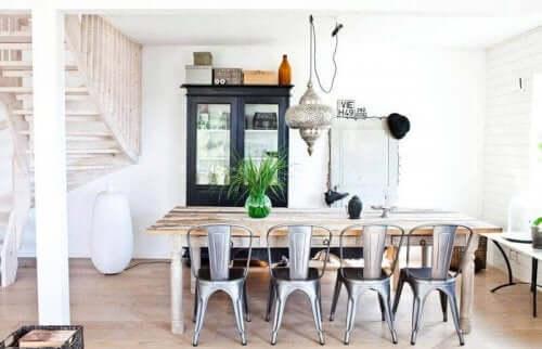 İki katlı evin salonunda geniş dikdörtgen masa etrafında sandalyeler