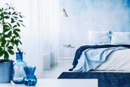 Açık mavi duvarlı vazo ve yatak örtülerinde mavi tonları kullanılmış oda