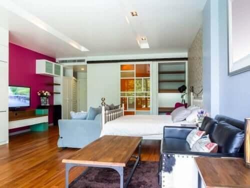 Bir duvarı farklı renk olan iki koltuklu yatak odası
