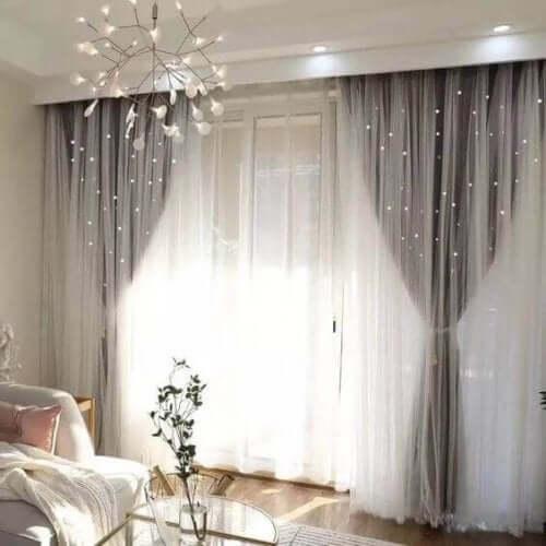 Tül perde ve gri perde takılı ferah oturma odası