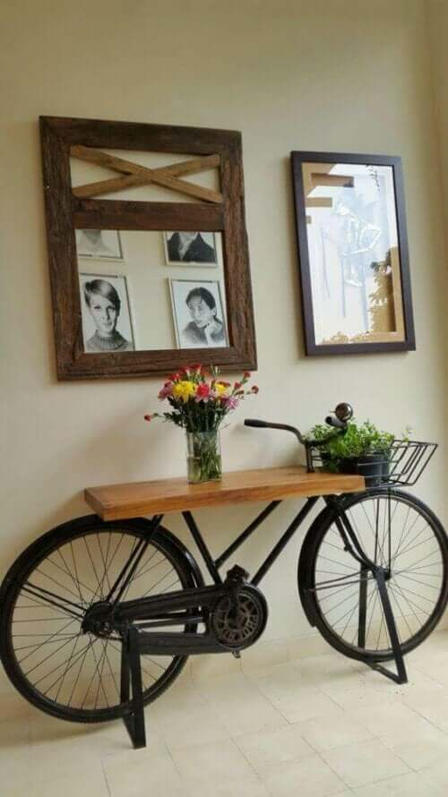 Bisiklet gövdesi üstüne yapılmış sehpa ve duvarda çerçeveler