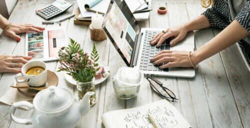 Masa üstünde kahveler, bitkiler ve bilgisayarlar