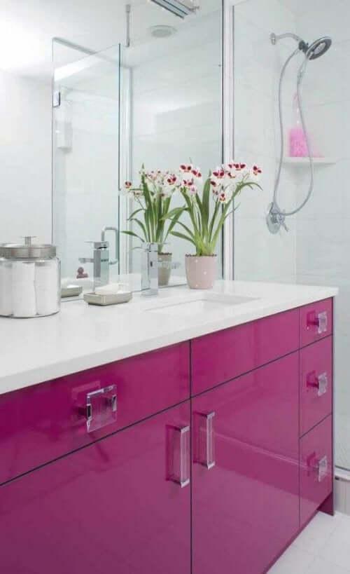 Tezgah üstünde çiçek olan banyo dolabı