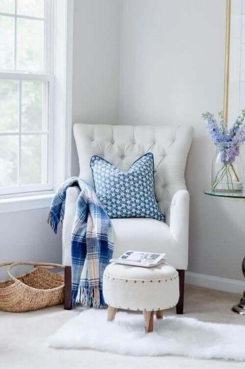 Beyaz koltuk ve mavi dekoratif ürünlerin olduğu okuma köşesi