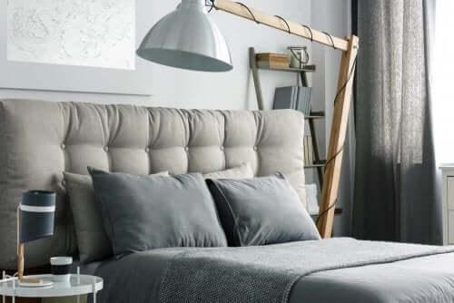 Gri tonlarda başlıklı yatak ve yatağın üstüne gelen abajur