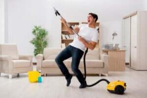 Adam neşeyle evini temizliyor.