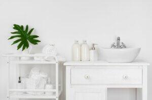 Küçük beyaz bir banyo dolabı ve üzerinde lavabonun yanında beyaz servis arabasında beyaz havlu ve sabunluklar