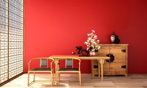 Sade kırmızı bir duvarın önünde açık renk ahşap mobilyalar