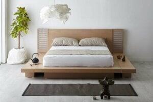 Ahşap bir yatak ve sade beyaz bir yatak odası