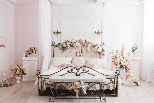 A wrought iron bed with pink flower decor