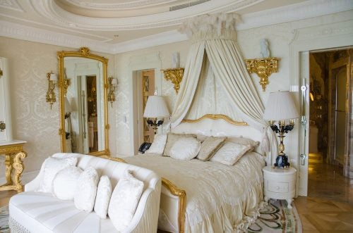 White and gold Victorian style bedroom with a canopy and gilded mirror
