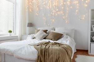 Bedrooms with white walls look even more beautiful when decorated with fairy lights.