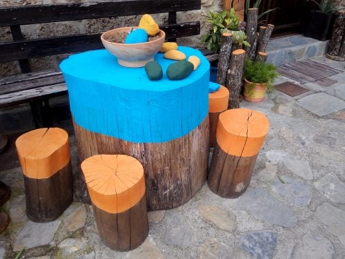 You could paint your tables made using tree trunks in different colors or even use varnish
