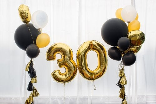"Black balloons and number balloons in gold that say ""30""."