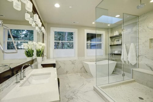 Large bright bathroom decorated in white marble.
