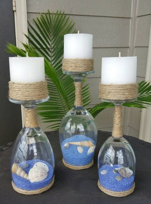 Use wine glasses, colored sand, seashells and candles to create beautiful jars with sand