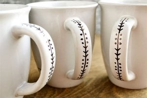 mugs with a black marker design on the handle