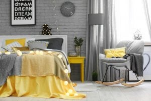 A bedroom with yellow pillows and blankets, contrasted with greys