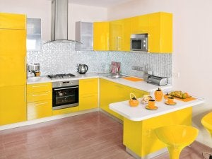 A kitchen with yellow cabinets and drawers