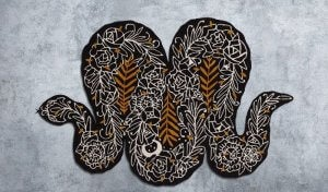An image shows an artistic design for a rug in the shape of a snake, with white and golden brown embroidery on a black surface.