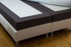 A picture shows a pair of twin bed frames connected to make a larger bed with mattresses on top.