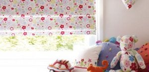 Floral print blinds half rolled up in a window in a child's bedroom.