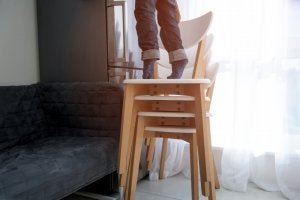 A person seen from the legs down is standing on their tip-toes on top of a stack of chairs, trying to reach something.