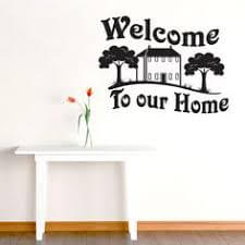 "You can use decals to decorate an entryway, in this case, one that says ""Welcome to our home,"" with a house and trees."
