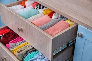 A picture showing a dresser with a couple drawers open, full of clothing.