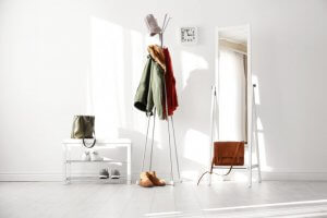 A picture shows an entryway painted white, with nothing but a shoe rack, a mirror, and a coat rack, and lots of empty space.