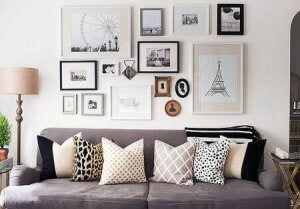 A living room shown with a big couch with lots of pillows, and lots of frames of different shapes and sizes on the wall above it.