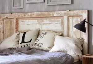 A reclaimed door is sitting behind a bed and acting as a headboard.
