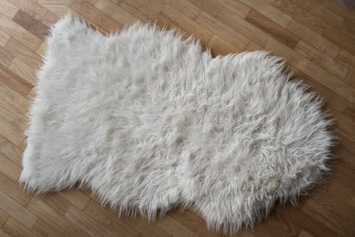 A white sheepskin rug on a timber floor