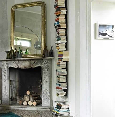 Stack of books on invisible shelves next to a fireplace