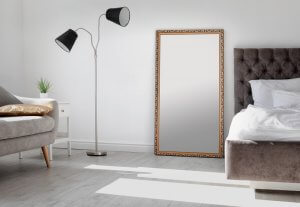 A picture shows a living room with grey, hard wood floors with a mirror anchored to the wall.