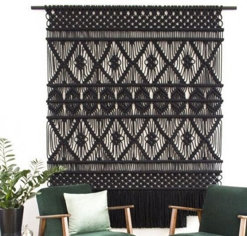 A large black macrame wall hanging in a turquoise themed decor