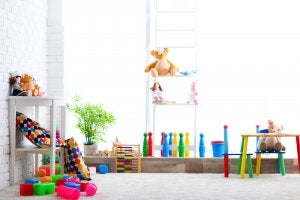 A brightly lit toy library with well organized shelves and tables and lots of colorful toys.