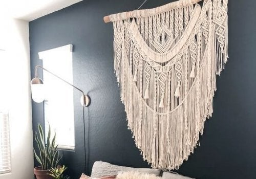 A macrame wall hanging is used instead of a bed headboard as a bedroom feature