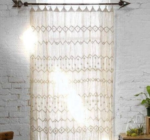 A white macrame curtain lets only diffused light into the room