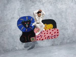 A person jumping in the air to pose with Misaki Kawai's rug.