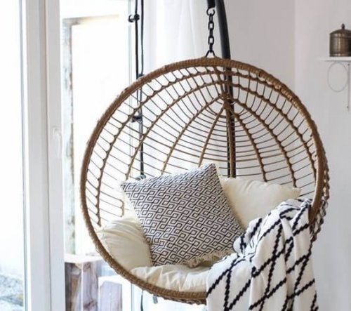 A round free standing swing with cushions and blankets