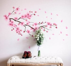 An entryway with decorated with wall decals that come together to look like a cherry blossom shedding its pink leaves.