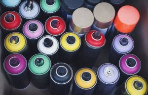 A bunch of spray paint cans with various top colors are bundled up in a small space, pictured from above.