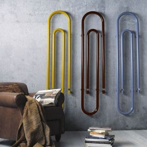 A picture showing vintage radiators snaking up a wall, painted in three different colors.