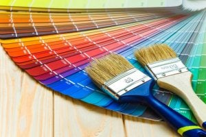 A pair of paint brushes is lying on top of a fanned out spread of paint swatches.